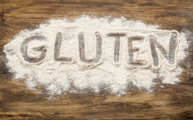 gluten word written in wheat flour on wooden board