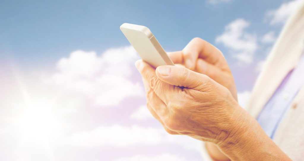 technology, age and people concept - close up of senior woman hands with smartphone texting message over blue sky and clouds background